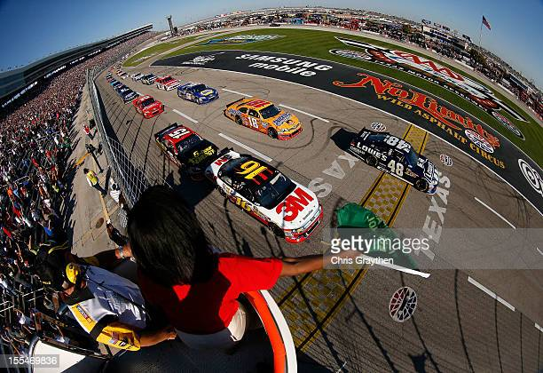 Greg Biffle driver of the 3M Ford and Jimmie Johnson driver of the Lowe's Chevrolet lead the field at the start of the NASCAR Sprint Cup Series AAA...