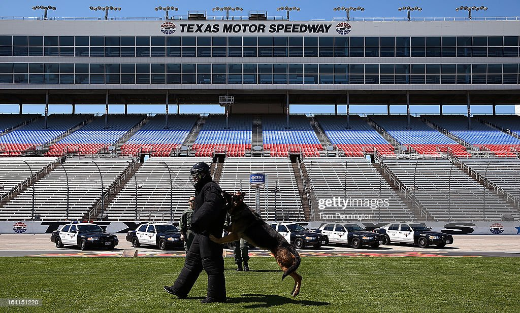 Greg Biffle, driver of the #16 3M Ford Fusion, runs from Rocky, a Fort Worth Police Department K-9, during an exhibition at Texas Motor Speedway on March 20, 2013 in Fort Worth, Texas.
