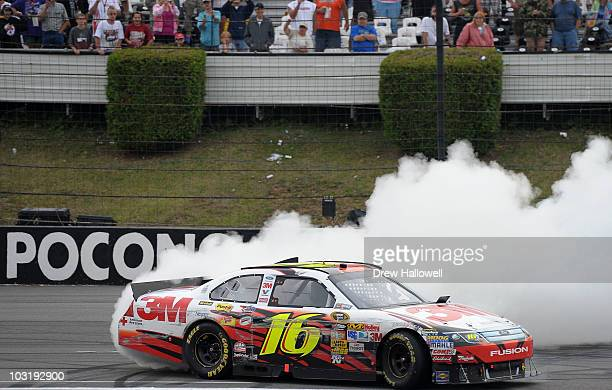 Greg Biffle driver of the 3M Ford performs a burnout after winning the NASCAR Sprint Cup Series Sunoco Red Cross Pennsylvania 500 at Pocono Raceway...