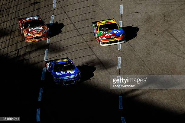 Greg Biffle driver of the 3M ScotchBlue Painter's Tape Ford leads Ryan Newman driver of the Haas Automation Chevrolet and Michael McDowell driver of...
