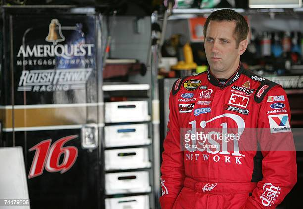 Greg Biffle driver of the Dish Network Ford looks on in the garage during practice for the NASCAR Nextel Cup Series Pocono 500 at Pocono Raceway on...