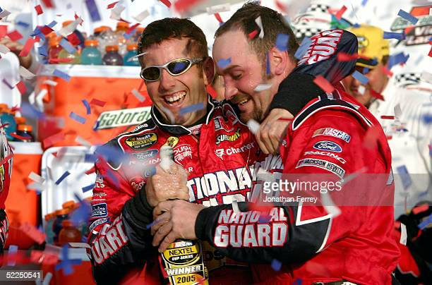 Greg Biffle driver of the PostIt Ford celebrates in victory lane with a crew memberduring the NASCAR Nextel Cup Auto Club 500 on February 27 2005 at...
