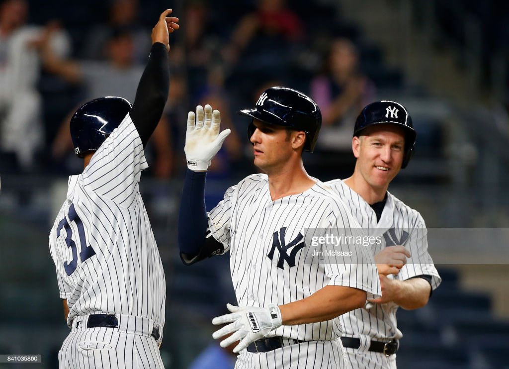 Greg Bird #33 of the New York Yankees celebrates his ninth inning three run home run against the Cleveland Indians with teammates Aaron Hicks #31 and Todd Frazier #29 (R) in the second game of a doubleheader at Yankee Stadium on August 30, 2017 in the Bronx borough of New York City.