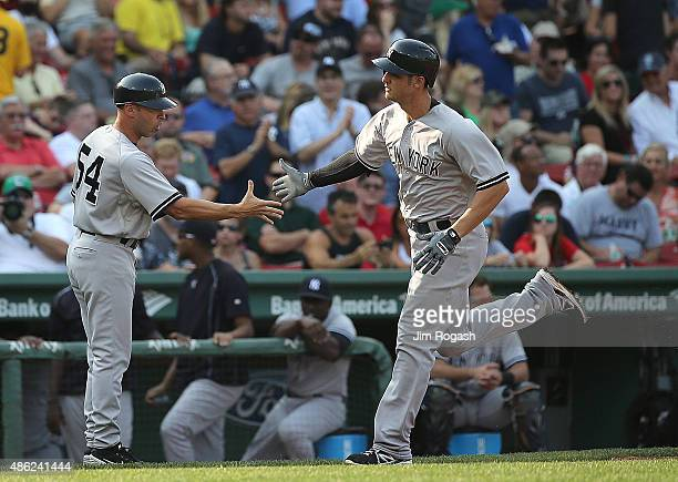Greg Bird of the New York Yankees is congratulated by third base coach Joe Espada after his home run in the second inning against he Boston Red Sox...