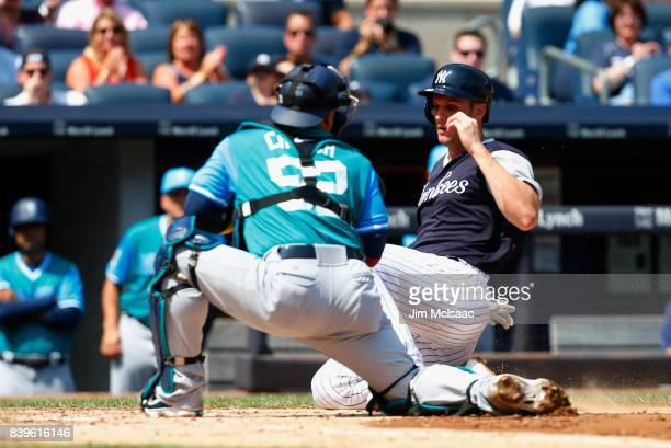 Greg Bird of the New York Yankees is tagged out at home by Carlos Ruiz of the Seattle Mariners during the second inning at Yankee Stadium on August...