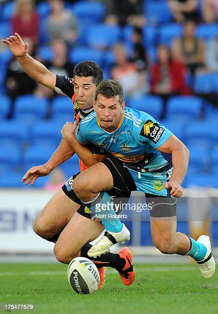 Greg Bird of the Titans and Braith Anasta of the Tigers compete for the ball during the round 21 NRL match between the Gold Coast Titans and the...