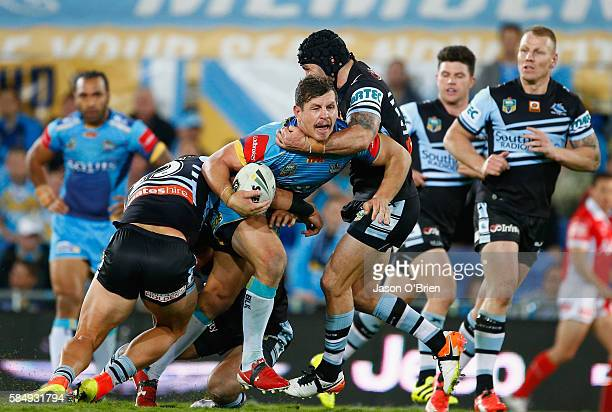 Greg Bird of the Titans is tackled by Michael Ennis of the Sharks during the round 21 NRL match between the Gold Coast Titans and the Cronulla Sharks...