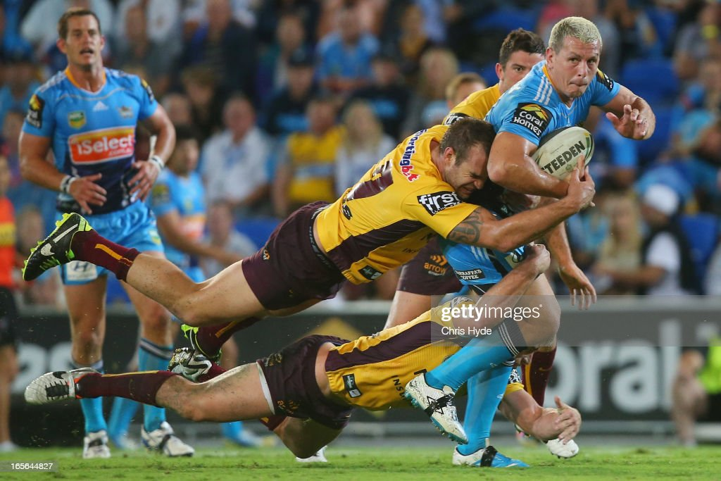 Greg Bird of the Titans is tackled during the round five NRL match between the Gold Coast Titans and the Brisbane Broncos at Skilled Park on April 5, 2013 in Gold Coast, Australia.