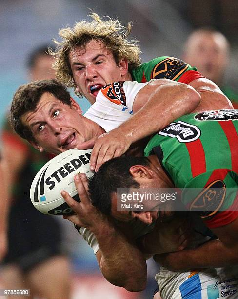 Greg Bird of the Titans is tackled heavily by Dave Tyrell and John Sutton of the Rabbitohs during the round two NRL match between the South Sydney...