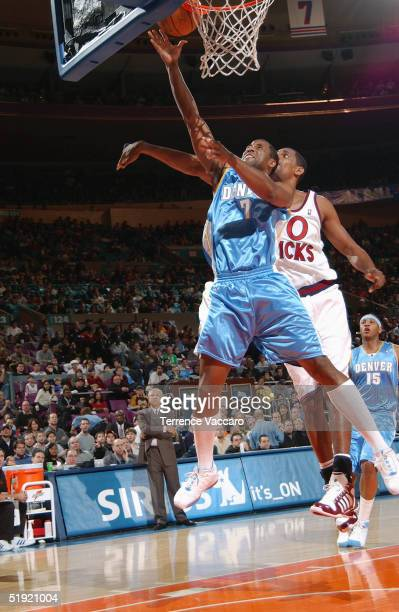 Greg Buckner of the Denver Nuggets shoots past Kurt Thomas of the New York Knicks during the game at Madison Square Garden on December 12 2004 in New...