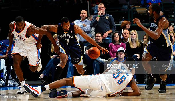 Greg Buckner of the Memphis Grizzlies steals the basket ball from Kevin Durant and Desmond Mason of the Oklahoma City Thunder at the Ford Center on...