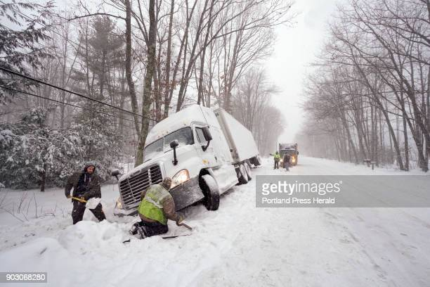 Greg Campbell left digs out the front of his tractor trailer while Keith Proctor of Rays Truck Service tries to fix a tow hook on Campbells truck...