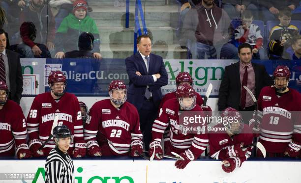 Greg Carvel head coach of the Massachusetts Minutemen stands behind the bench during a game against the Massachusetts Lowell River Hawks during NCAA...