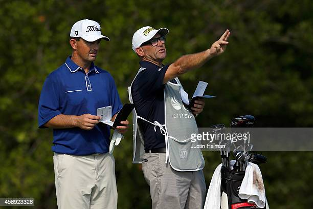 Greg Chalmers of Australia talks with his caddie prior to hitting his tee shot on the second hole during the first round of the OHL Classic at...