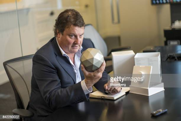 Greg Clark chief executive officer of Symantec Corp holds a Norton Core WIFI router as he speaks during an interview in San Francisco California US...