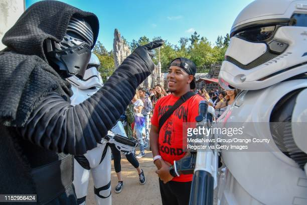Greg Daniels is questioned by Kylo Ren and stormtroopers during at Black Spire Outpost on opening day at Star Wars Galaxyu2019s Edge at Disneyland in...