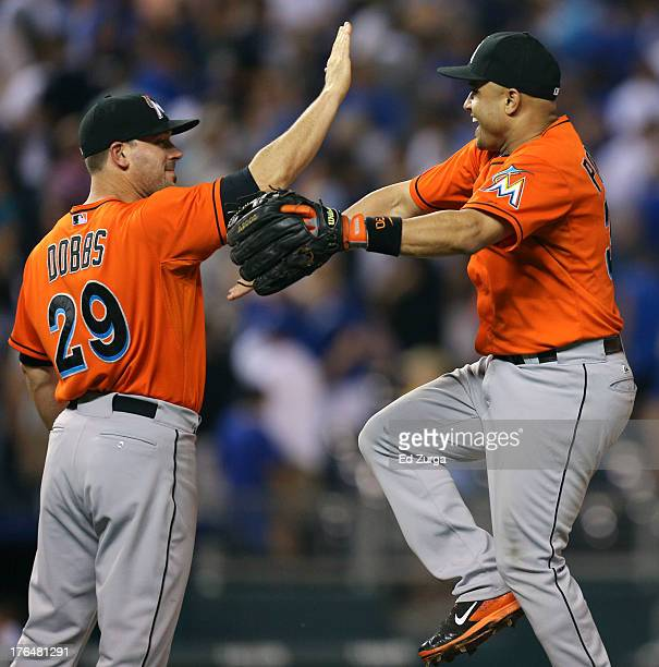 Greg Dobbs of the Miami Marlins and Placido Polanco celebrate a 10 win over the Kansas City Royals in 10 innings at Kauffman Stadium August 13 2013...