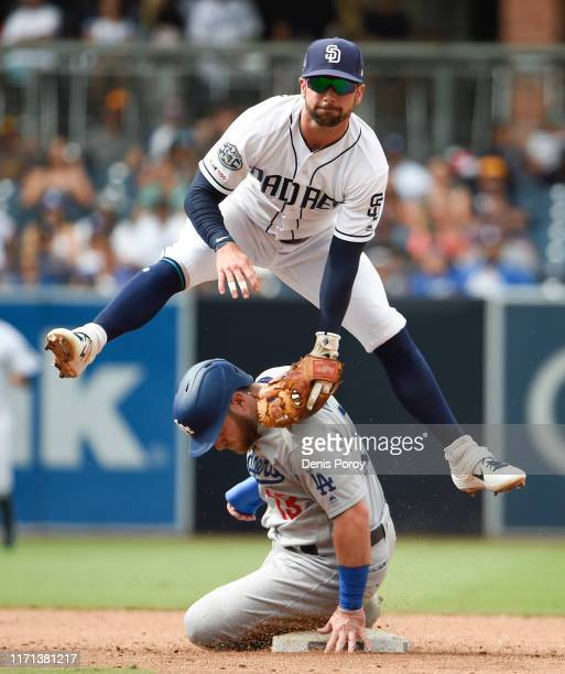 Greg Garcia of the San Diego Padres jumps over Max Muncy of the Los Angeles Dodgers as he turns a double play during the the ninth inning of a...