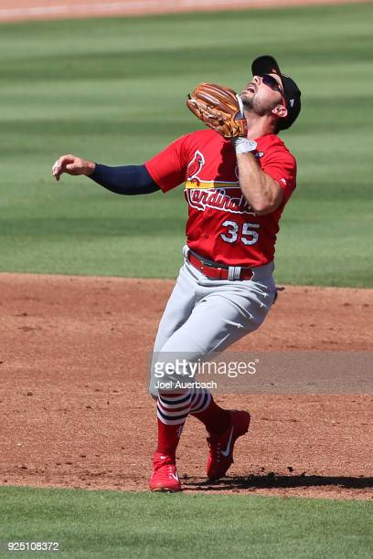 Greg Garcia of the St Louis Cardinals fields a pop fly hit by the Miami Marlins during a spring training game at Roger Dean Chevrolet Stadium on...