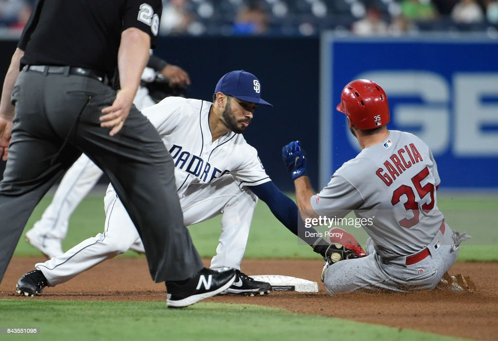 Greg Garcia #35 of the St. Louis Cardinals is tagged out by Carlos Asuaje #20 of the San Diego Padres as he tries to steal second base during the seventh inning of a baseball game at PETCO Park on September 6, 2017 in San Diego, California.