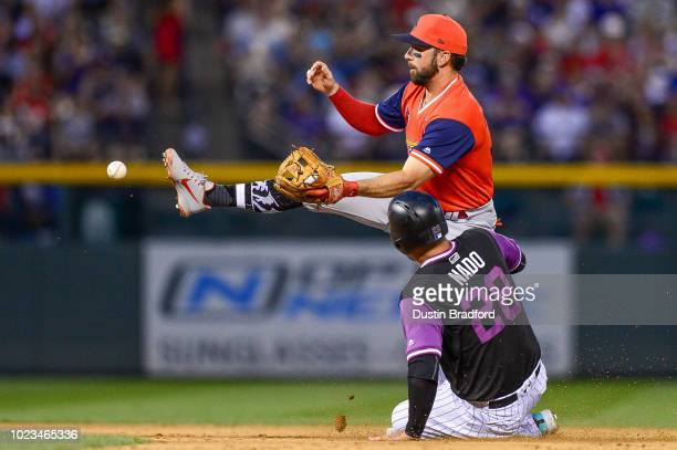 Greg Garcia of the St Louis Cardinals loses the ball attempting to turn a double play after forcing out Nolan Arenado of the Colorado Rockies at...