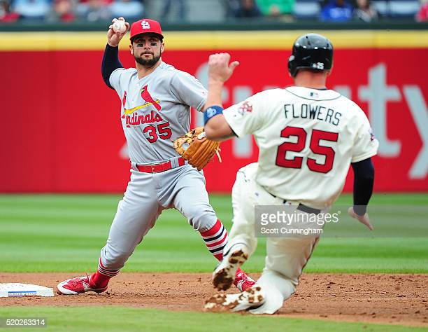 Greg Garcia of the St Louis Cardinals turns a second inning double play against Tyler Flowers of the Atlanta Braves at Turner Field on April 10 2016...