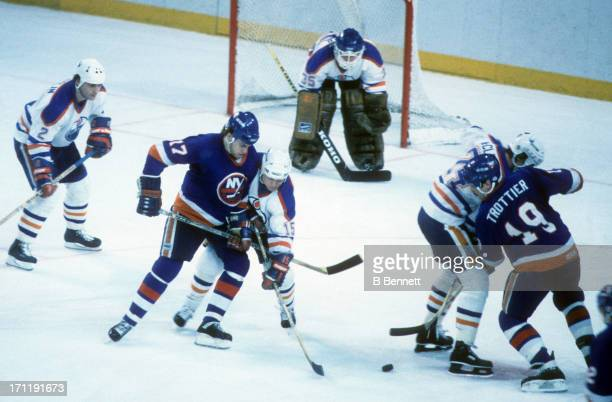 Greg Gilbert and Bryan Trottier of the New York Islanders battle with Pat Conacher and Kevin McClelland of the Edmonton Oilers for the puck during...