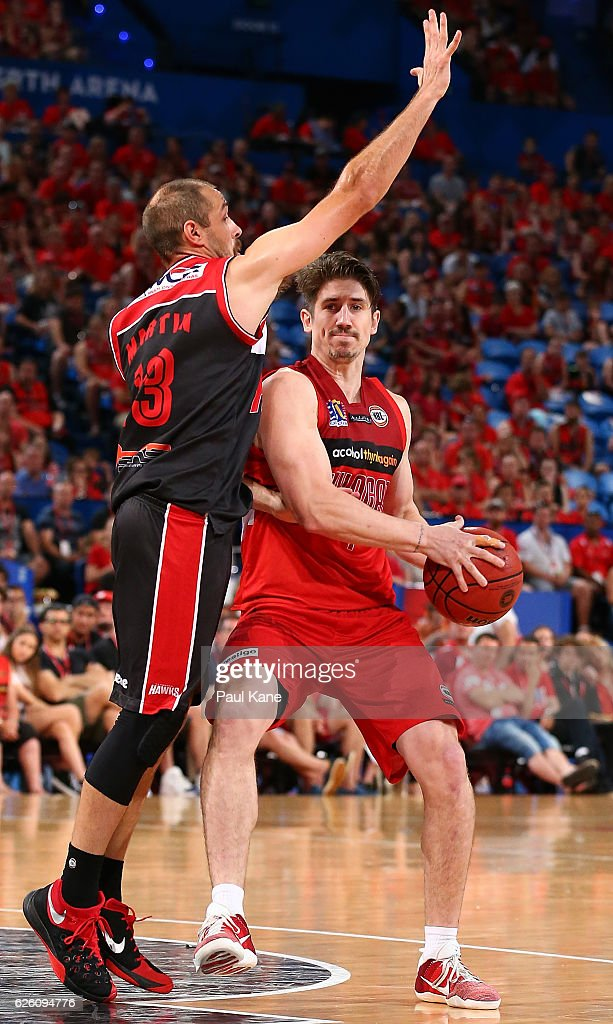Greg Hire of the Wildcats looks to pass the ball against Rhys Martin of the Hawks during the round eight NBL match between the Perth Wildcats and the Illawarra Hawks at the Perth Arena on November 27, 2016 in Perth, Australia.