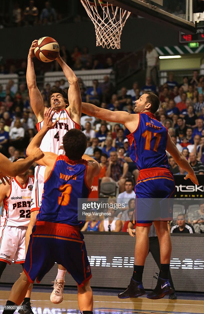 Greg Hire of the Wildcats tries to score while being challenged by Anthony Petrie of the 36ers during the round six NBL match between the Adelaide 36ers and the Perth Wildcats at Adelaide Arena on November 11, 2012 in Adelaide, Australia.