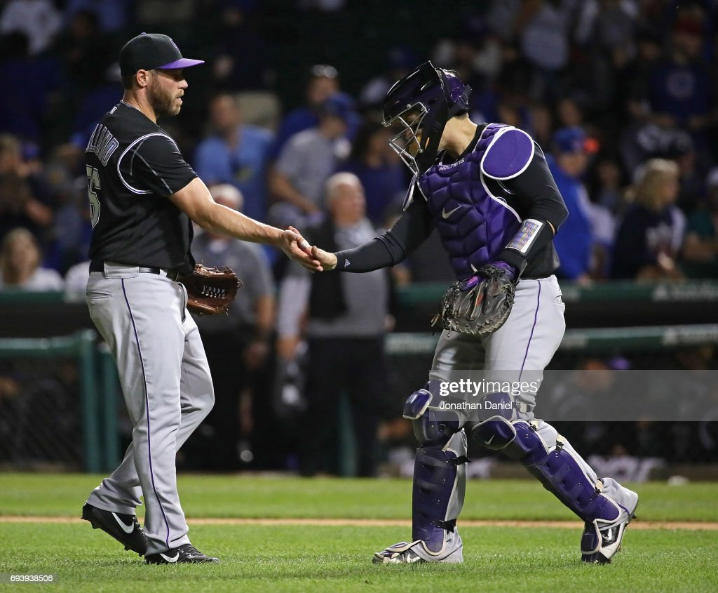Greg Holland #56 (L) and Tony Wolters #14 of the Colorado Rockies celebrate a win over the Chicago Cubs against the Chicago Cubs at Wrigley Field on June 8, 2017 in Chicago, Illinois. The Rockies defeated the Cubs 4-1.