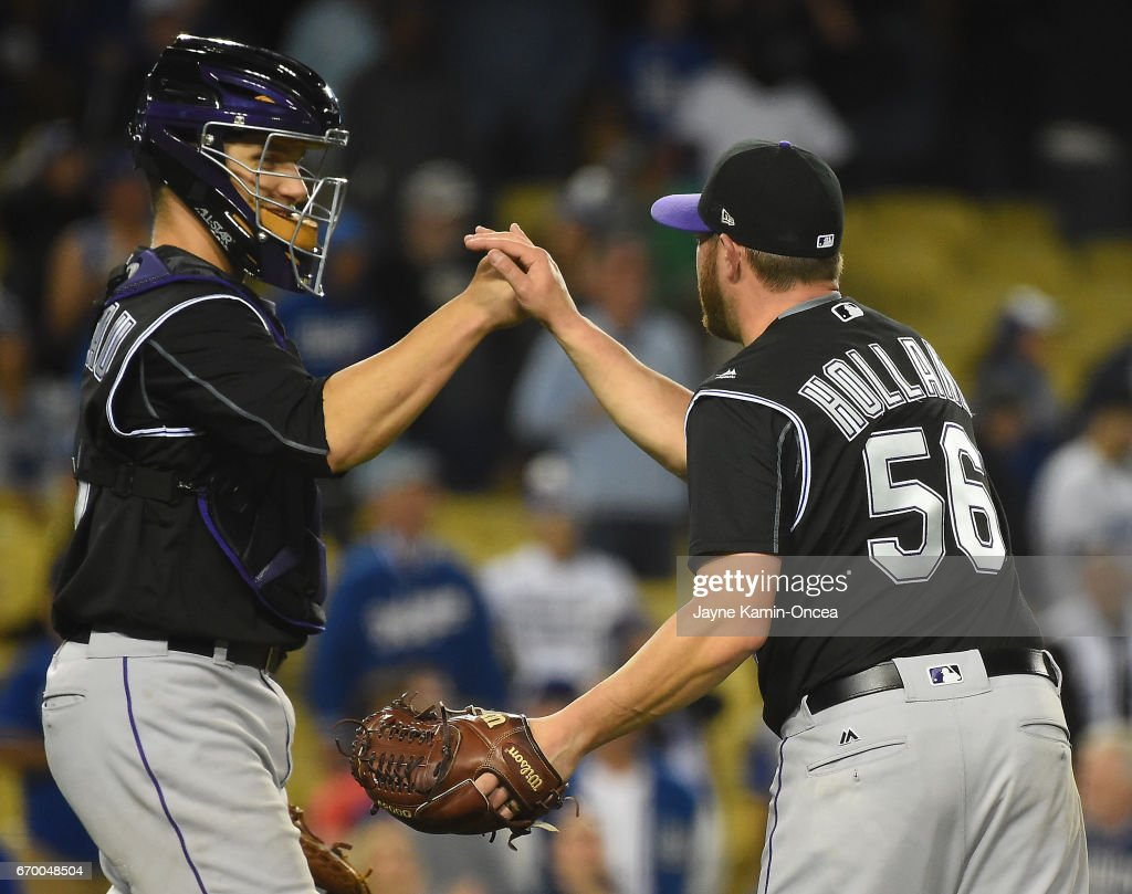 Greg Holland #56 of the Colorado Rockies gets a high five from Dustin Garneau #13 of the Colorado Rockies after the ninth inning as they defeated the Los Angeles Dodgers 4-3 at Dodger Stadium on April 18, 2017 in Los Angeles, California.