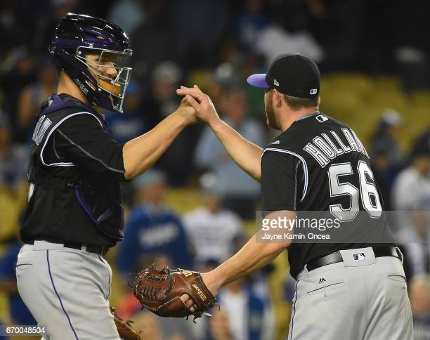 Greg Holland of the Colorado Rockies gets a high five from Dustin Garneau of the Colorado Rockies after the ninth inning as they defeated the Los...