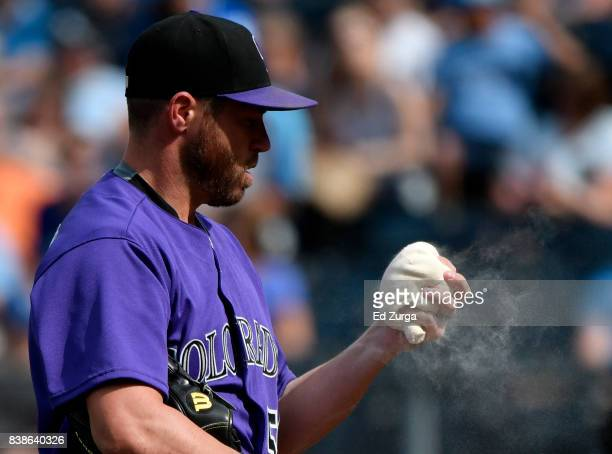 Greg Holland of the Colorado Rockies uses the rosin bag before throwing against the Kansas City Royals in the ninth inning at Kauffman Stadium on...