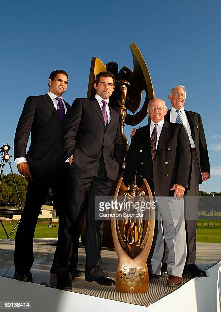 Greg Inglis and Cameron Smith of the Melbourne Storm pose with rugby league legends Authur Summons and Norm Provan and the premiership trophy during...