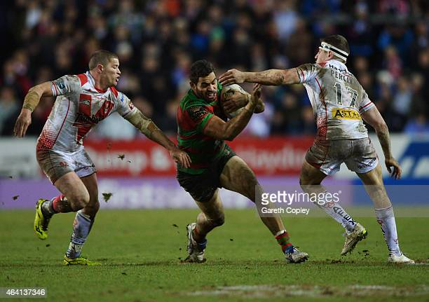 Greg Inglis of South Sydney Rabbitohs goes between Travis Burns and Mark Percival of St Helens during the World Club Challenge match between St...