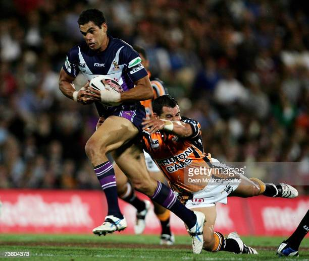 Greg Inglis of Storm is tackled by Ben Galea of Tigers during the round one NRL match between the Melbourne Storm and the Wests Tigers at Olympic...