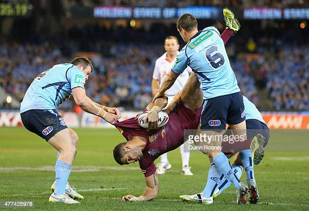 Greg Inglis of the Maroons is tackled by Josh Morris and Mitchell Pearce of the Blues during game two of the State of Origin series between the New...