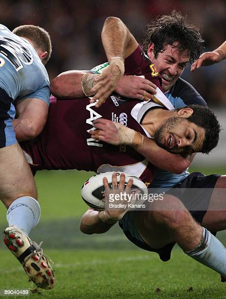 Greg Inglis of the Maroons is wrapped up in a tackle by Trent Waterhouse of the Blues during game three of the ARL State of Origin series between the...