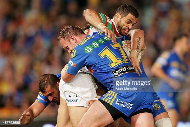 Greg Inglis of the Rabbitohs is tackled by David Gower and Tim Mannah of the Eels during the round four NRL match between the Parramatta Eels and the...