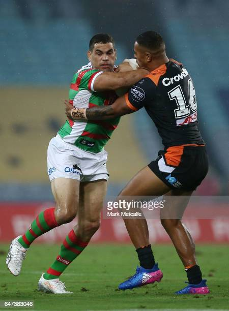 Greg Inglis of the Rabbitohs is tackled by Michael CheeKam of the Tigers during the round one NRL match between the South Sydney Rabbitohs and the...