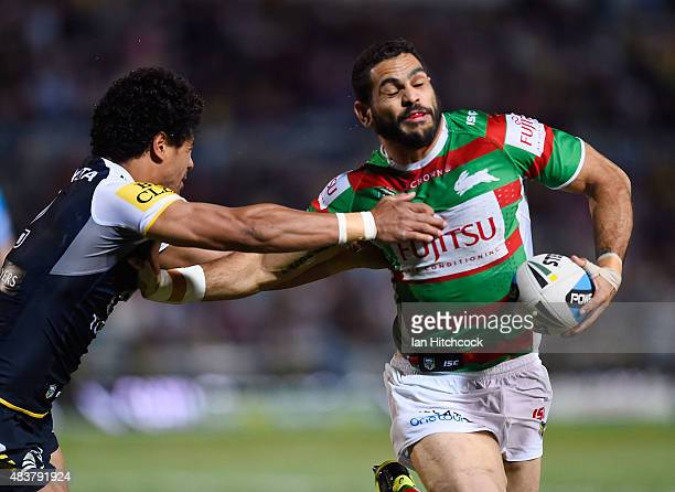 Greg Inglis of the Rabbitohs pushes aside Matthew Wright of the Cowboys on his way to score a try during the round 23 NRL match between the North...