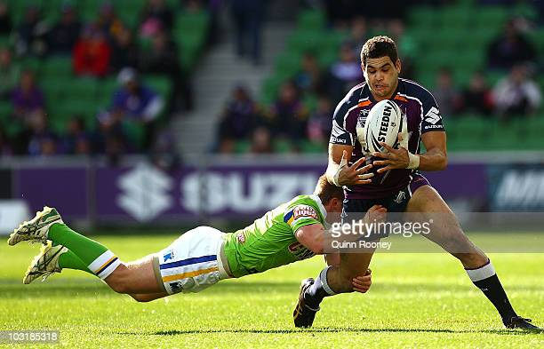 Greg Inglis of the Stormis tackled by Josh McCrone of the Raiders during the round 21 NRL match between the Melbourne Storm and the Canberra Raiders...