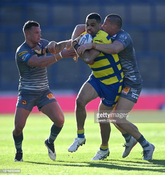 Greg Inglis of Warrington is tackled by Josh Drinkwater and Joel Tomkins of Catalans during the Betfred Challenge Cup quarter final between Catalans...