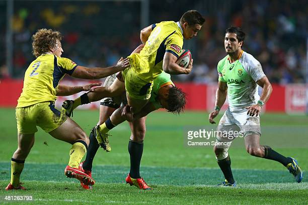 Greg Jeloudev of Australia is tackled during the Pool B match between Australia and South Africa during the 2014 Hong Kong Sevens at Hong Kong...