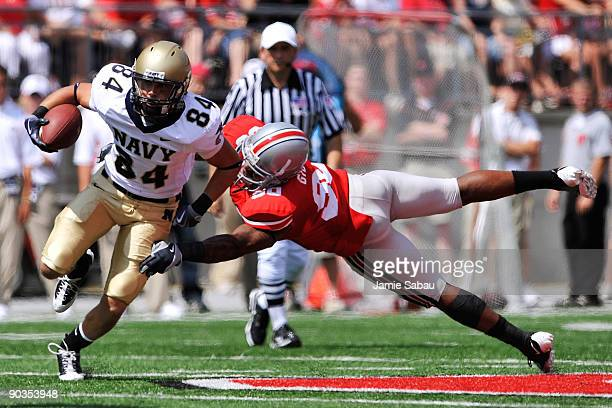Greg Jones of the Navy Midshipmen eludes the tackle of Thaddeus Gibson of the Ohio State Buckeyes at Ohio Stadium on September 5 2009 in Columbus...