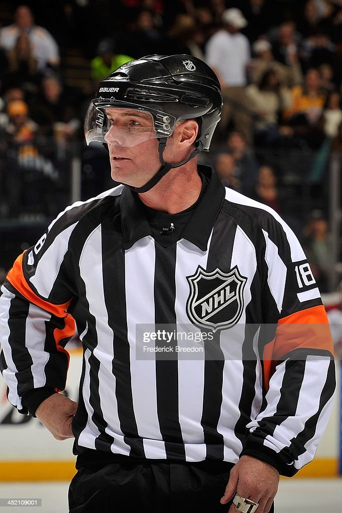 Greg Kimmerly #18 officiates a game between the Nashville Predators and the Phoenix Coyotes at Bridgestone Arena on November 25, 2013 in Nashville, Tennessee.