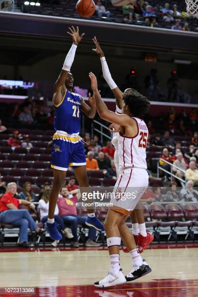 Greg Lee of the Cal State Bakersfield Roadrunners shoots the ball over Bennie Boatwright of the USC Trojans during a college basketball game at Galen...