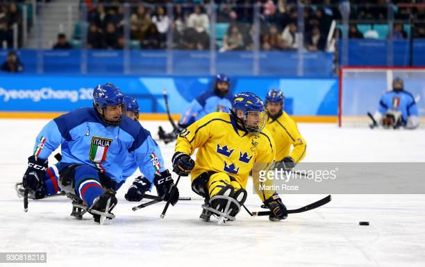 Greg Leperdi of Italy battles for the puck with Marcus Holm of Sweden in the Ice Hockey Preliminary Round Group A game between Italy and Sweden...