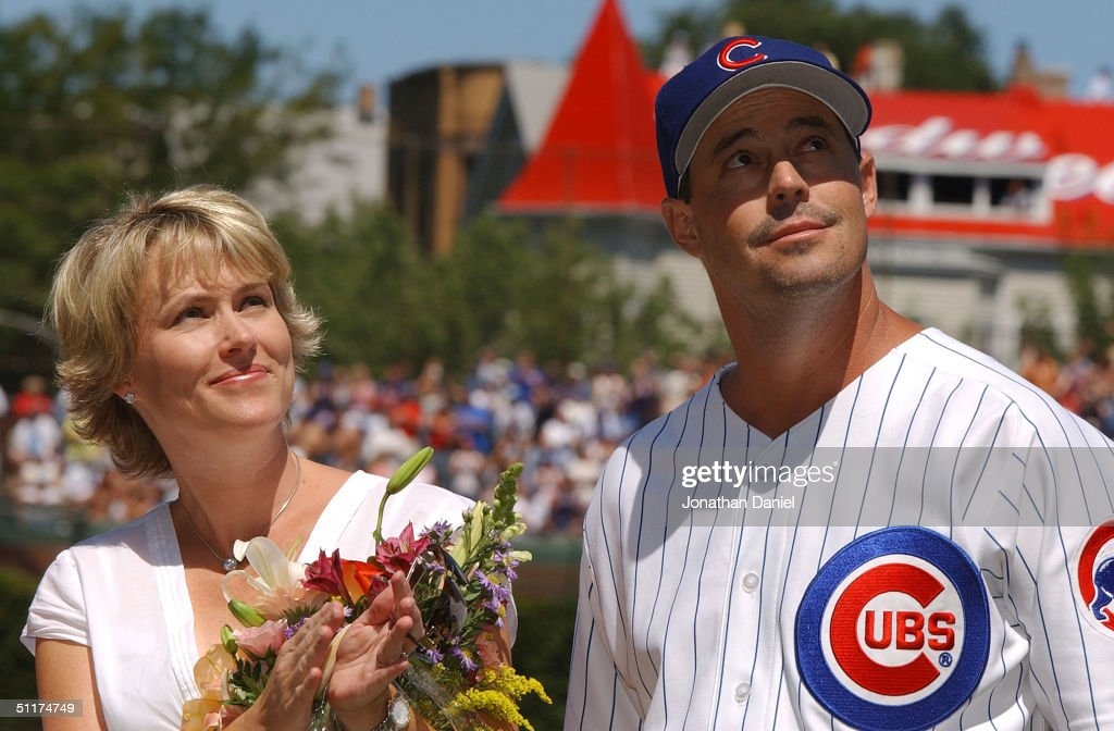 Greg Maddux of the Chicago Cubs and his wife Kathy look up at a new flag which will fly over Wrigley Field during a ceremony honoring his 300th career win before a game against the Los Angeles Dodgers August 15, 2004 at Wrigley Field in Chicago, Illinois.