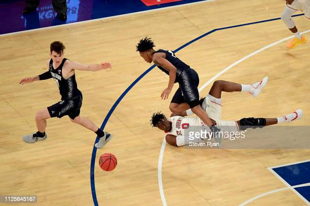 Greg Malinowski and James Akinjo of the Georgetown Hoyas battles for the ball with Sedee Keita of the St John's Red Storm at Madison Square Garden on...